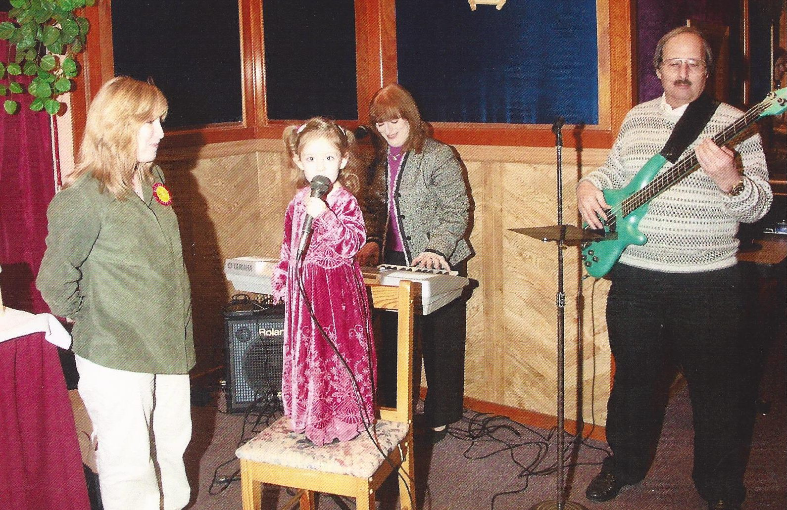 Alexa as a baby singing at her brother's baby naming. Her mother Sheri is to the left, her grandma Sandy is behind her playing the piano, and her Grandpa Shelley is to the right of her playing the guitar.